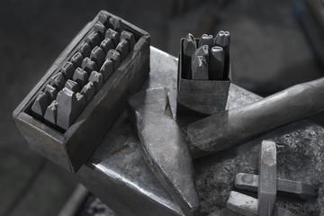 Punching tool and hammer on anvil at blacksmith shop