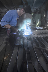 Blacksmith fusing garden gate in workshop
