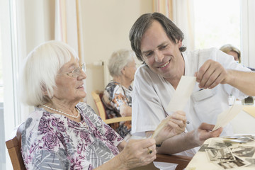 Caretaker watching photos with senior women at rest home