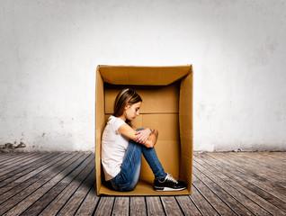 sad young woman inside a Box on a room