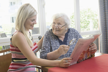 Senior woman reading newspaper with her daughter