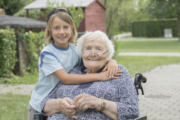 Senior woman on wheelchair with grandson at rest home park
