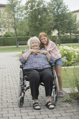 Senior woman on wheelchair with granddaughter at rest home park