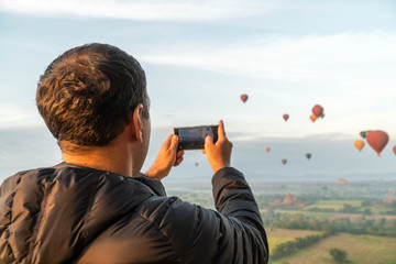 Male Tourist Taking Mobile Photo of Hot Air Balloons in Bagan, Myanmar