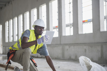 Construction worker using digital tablet at building site