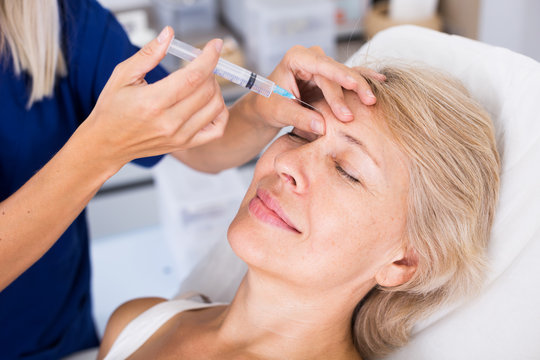 Senior woman getting facial injection