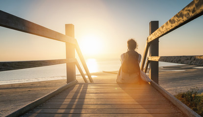 woman is sitting on a wooden path to the Baltic sea at sunset and relaxe the ocean view Wall mural