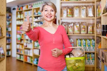 Attractive woman customer displaying purchased organic food