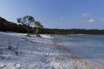 weißer Sand am Ufer eines Badesees mit Touristen im Hintergrund