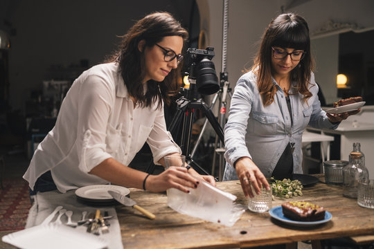 Pregnant woman with a colleague working on a food photo shoot