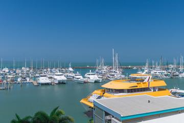 Yachthafen mit orangenem Ausflugsboot im Vordergrund