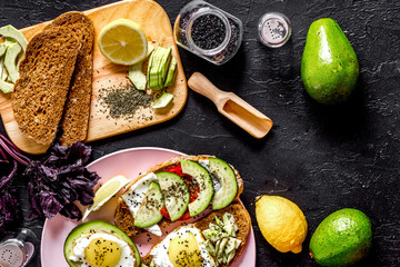 Light breakfast. Sandwiches with avocado and fried eggs on black
