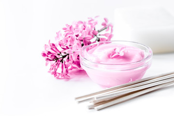 lilac cosmetics with flowers and spa set on white table backgrou