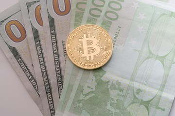 Bitcoin on dollar and euro bills close up view