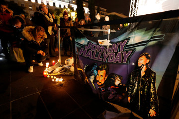 A woman lights a candle to pay tribute to the late French singer and actor Johnny Hallyday in Nice