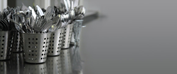 cutlery (knives, forks, spoons) in metal containers on a gray countertop
