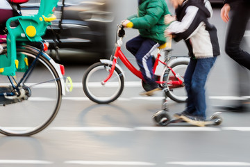 children with bicycles crossing a street