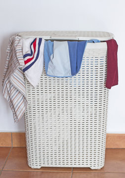 A dirty laundry hamper with some clothes coming out from the cover.
