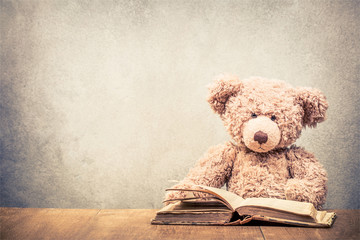 Retro Teddy Bear toy sitting at the old wooden desk with old book front concrete wall background. Vintage instagram style filtered photo