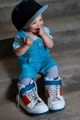 little boy in large sneakers and big hat .Hip-Hop Style. fashion children. Young Rapper. 1 years old