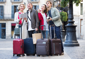 Two couples with luggage search for sights on map