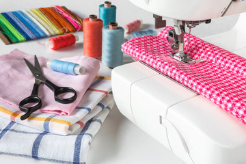 Multicolored sewing thread, sewing machine, scissors, buttons and various accessories for a tailor on a light background with copy space on a white round sheet with an inscription handmade