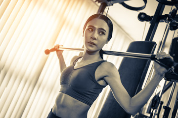 asian strong woman fit and firm healthy concept lifting dumbbell at gym