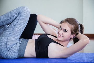 woman friend in fitness health center woth stretch action pose on yoga mat