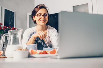 Woman has breakfast and watch laptop on kitchen