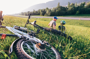 Father and son relax in green grass aftwr bicykle walk