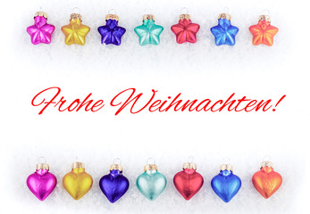 Colorful Christmas tree decorations on snow with Christmas greetings in German, which means Merry Christmas, white background
