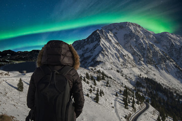 person turned away in front of the Northern Lights on the mountains