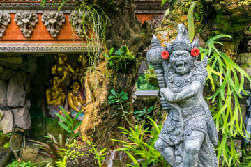 warrior figure of stone in a traditional garden balinese. indonesia. bali. ubud