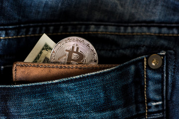 US bucks and bitcoin coin in a leather wallet inside jeans pocket.