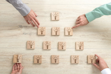 Four business people placing wooden blocks with light bulbs in a form of a pyramid