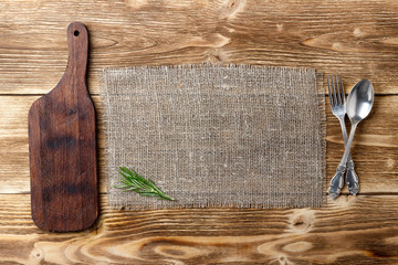 Cooking background concept. Vintage cutting board, sackcloth and cutlery. Top view with copy space.