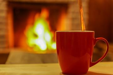 Mug  of tea, on wooden table, before  fireplace, defocused.