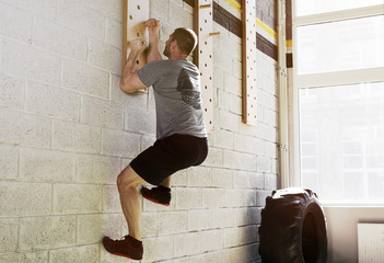 Man exercise on peg board in gym