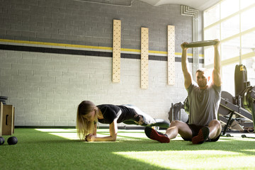 Man and woman training in gym together