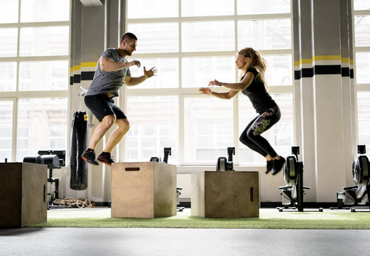 Man and woman jumping on boxes in gym