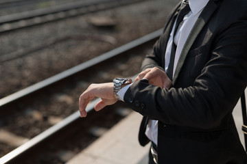 Businessman looking at the time on his wrist watch at train station background.
