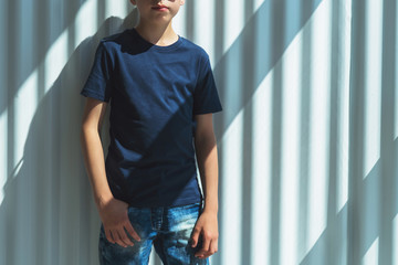 Front view. Young hipster boy in sunglasses dressed in black t-shirt is stands indoor against white wall. Mock up. Space for logo, text, image.