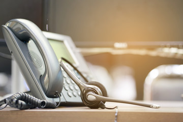 close up soft focus on headphone of call center with telephone devices at office desk for customer service support concept