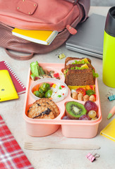Lunch box with sandwiches, vegetable salad and fresh fruits and rice on the table near school backpack