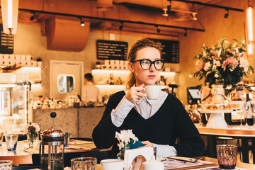 Young business woman in glasses sits in a cafe at a table, drinks coffee, holds smartphone in her hand. The girl is having breakfast in the restaurant,waiting for friends, colleagues. Resting, relax.