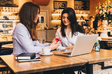 Two young businesswomen sitting in cafe at table and using laptop, working, blogging. Girls are looking at monitor and smiling. Students studying. On desk paper notebook. E-learning, online marketing.