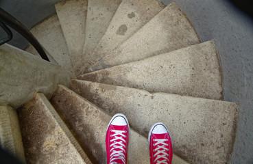 Rote Sneaker auf Wendeltreppe beim Abwärtsgehen