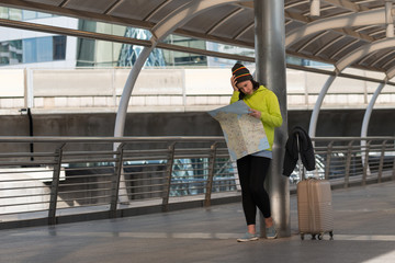 female tourist with suitcase exploring map. she headache finding way to hotel while standing in city building