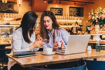 Two young happy women are sitting in cafe at table in front of laptop, using smartphone and laughing. On table paper notebook and cup of coffee. Girls are blogging, working, studying, learning online.