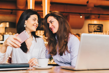 Two young happy women are sitting in cafe at table in front of laptop, using smartphone and smiling. On table paper notebook and cup of coffee. Girls are blogging, working, studying, learning online.